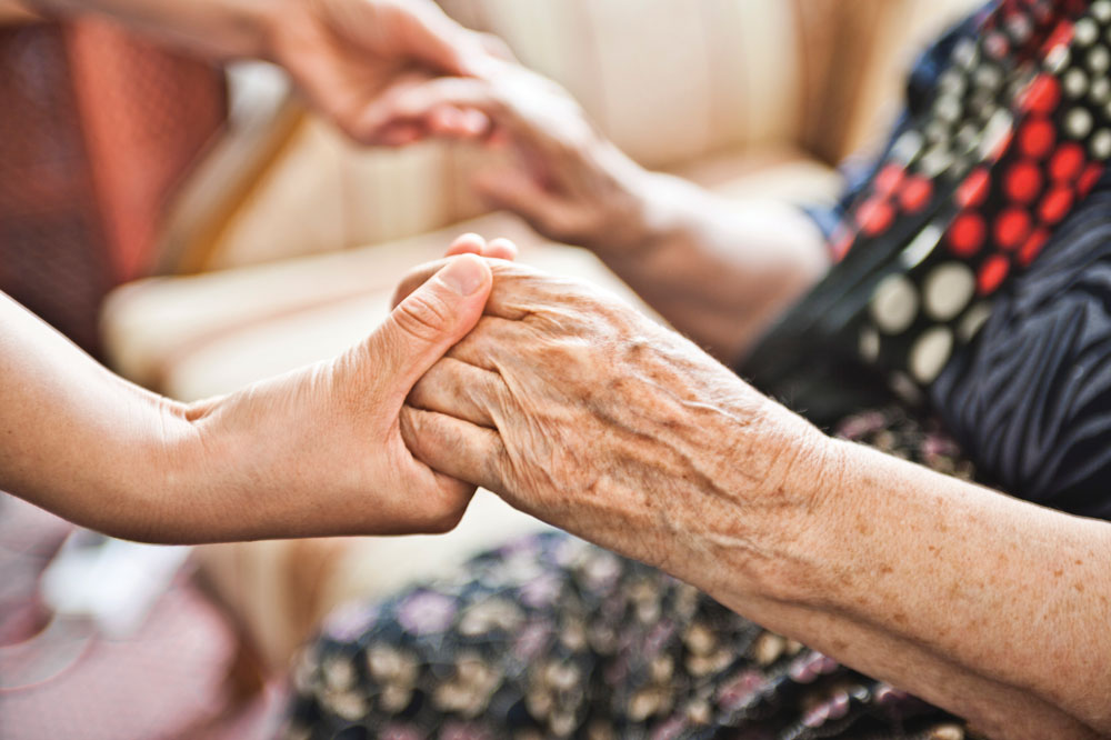 Senior living resident holding the hands of young adult